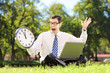 Angry businessman with laptop sitting on grass looking at clock