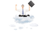 Young happy businessman with suitcase riding on clouds
