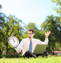 Angry man with laptop sitting on grass and looking at clock