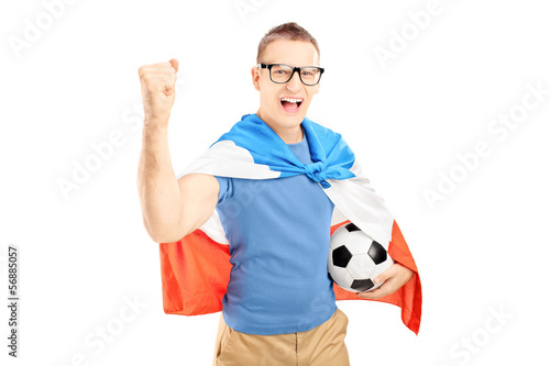 Euphoric male fan holding a soccer ball and flag of Holland