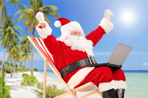 Happy Santa Claus sitting on a chair with laptop and gesturing