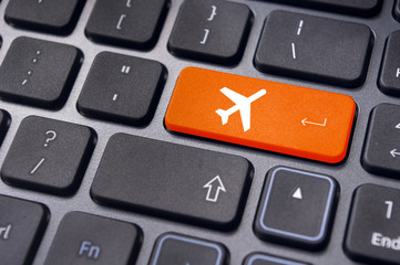 online booking of flight ticket, with plane sign on keyboard