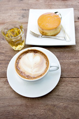 caramel custard cake and cup of coffee on wood background