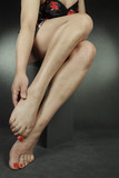Woman wearing nightie massaging feet