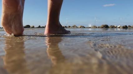 Beautiful women's feet in the surf