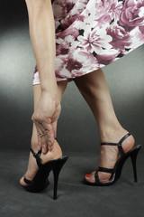 Woman feet wearing  dress and high heel shoes