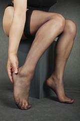 Woman sitting massaging aching feet