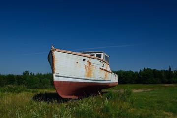 Old lobster boat in an empty farm field