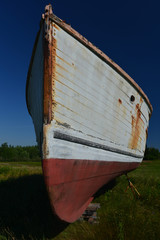Rusting lobster boat in a field