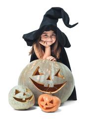 little witch hiding behind pumpkins
