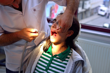 A male dentist examining a young girls teeth
