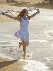 Young girl running at the beach