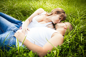 Sexy girl kissing her boyfriend on grass