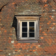 Window of attic on old tiled roof.
