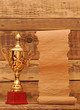 gold trophy cup with blank old paper scroll over wooden backgrou