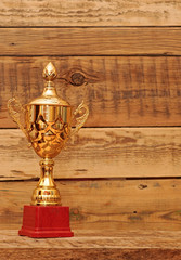 gold cup over wooden background
