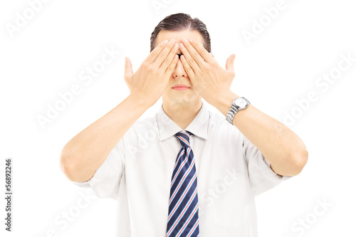 Young man with hands over his eyes