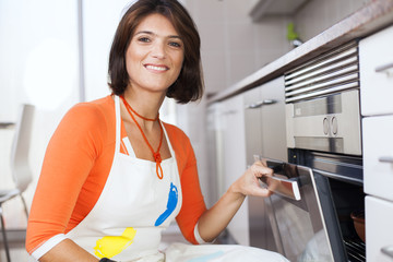 Woman opening the kitchen oven