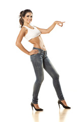 pretty girl with bare belly in tight jeans shows a direction