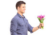 Smiling guy holding flowers