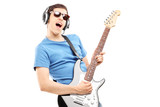 Male musician with headphones playing an electric guitar