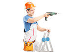 Repairman with a drilling machine on a ladder