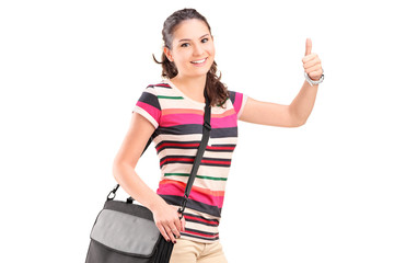 Female college student with a shoulder bag giving a thumb up