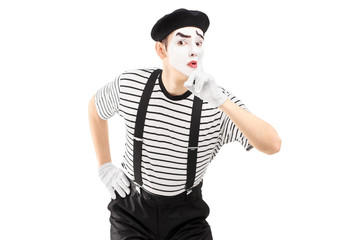 Male mime artist gesturing silence with a finger on his mouth