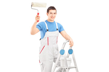 Male painter holding a roller and standing on a ladder