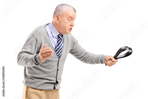 Angry mature man holding a belt and threatening