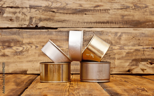 pile of tin cans on old wooden table