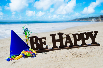 """Sign """"Be Happy"""" with Birthday decorations on the beach"""