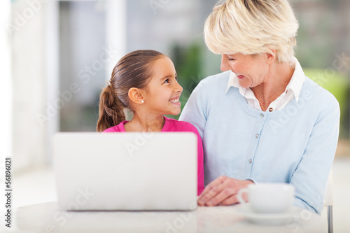 little girl and grandma using laptop