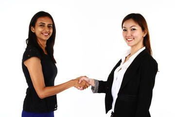 Two happy young Asian business women shaking hands