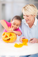 little girl cleaning her halloween pumpkin with granny