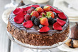 Chocolate cake with strawberries. Birthday party table, wood