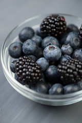 Close-up of glass bowl full of ripe blackberries and blueberries