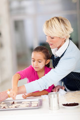 little girl and grandmother baking cookies