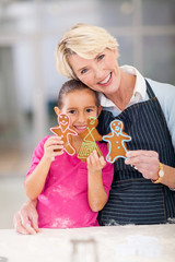 senior woman with granddaughter holding just baked gingerbread c
