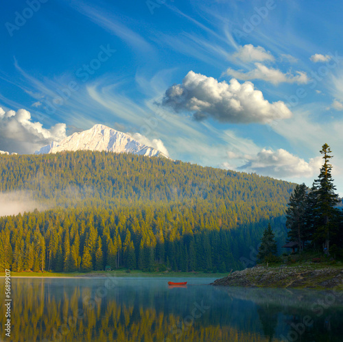 Landscape with blue sky, mountains, lake and lonely boat. Durmit