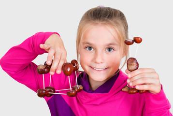 Mädchen  präsentiert Kastanienfiguren