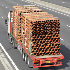 Truck fully loaded with plastic pipes of various diameters