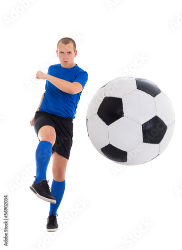 young attractive soccer player in blue uniform kicking ball isol