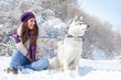 Young woman with her dog in snow