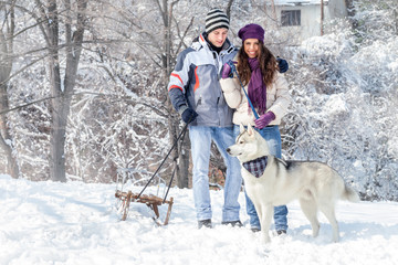 Couple with dog in snowy forest