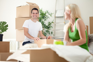 excited couple in new home unpacking boxes