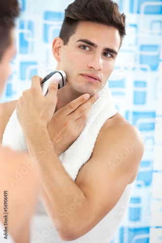 Young guy shaving his beard off with an electric shaver
