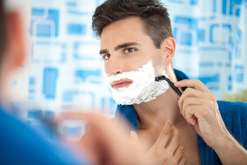 Young man shaving using a razor