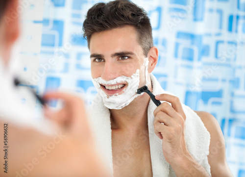 Happy laughing man shaving his face