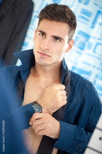 businessman getting dressed in bathroom